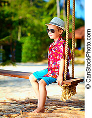 cute stylish boy on swings on the beach
