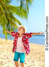 young fashionable boy enjoys life on tropical beach