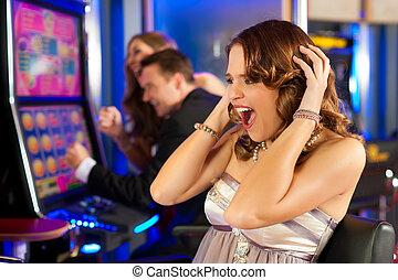 Friends in Casino on a slot machine; the woman in front...