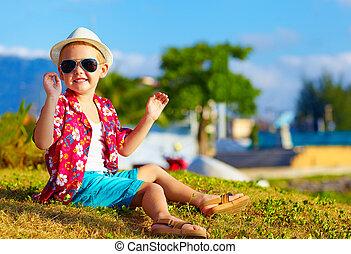 happy fashionable kid on summer meadow