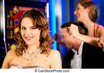 Friends in Casino on a slot machine; a woman is looking into...