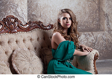 young attractive woman in green dress sits on a beautiful...