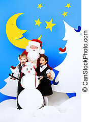 christmas night - Santa Claus standing with happy children...