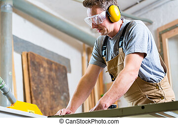 Carpenter using electric saw in carpentry - Carpenter...