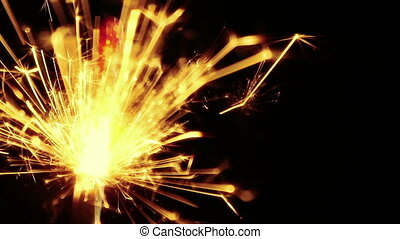 close-up of firework sparkler burning on black background,...