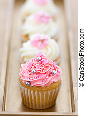 Pink and white cupcakes arranged on a tray