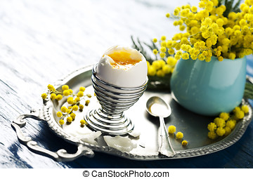 Boiled egg - Open soft boiled egg on tray with mimosa...