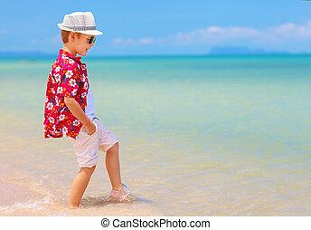 cute boy, kid playing in waves on summer beach