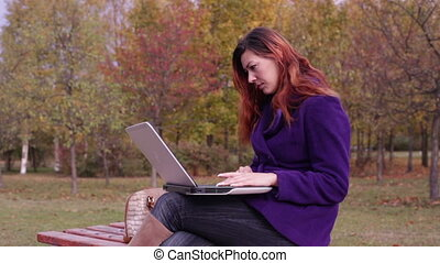 Bench in autumn park. A woman typing on a laptop.