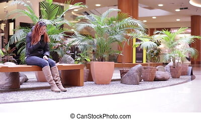 Girl talking on the phone on a bench in the mall