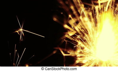 man lights up sparkler fireworks burning on a black...