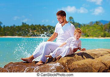 water splashing on laughing father and son