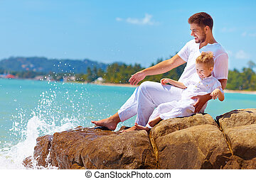 water splashing on laughing father and son on rocky coast