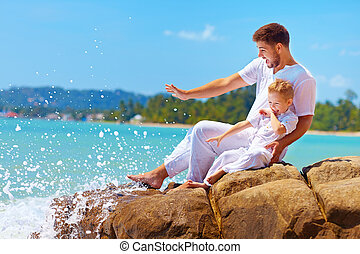 water splashing on happy father and son on vacation