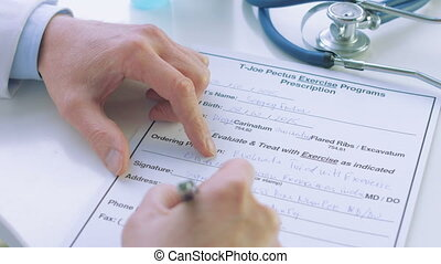 close up of male doctor hand writing prescription - close up...