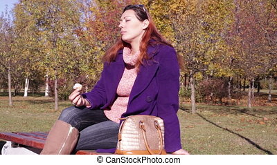 The girl eats ice cream on a bench in the park - Woman...