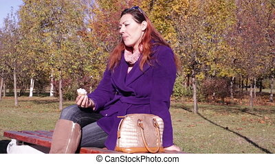 Woman eating ice cream on a bench in the park - The girl...