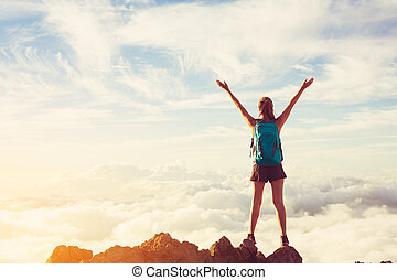Happy Woman Hiker With Open Arms at Sunset on Mountain Peak...