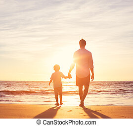 Father and Son Walking Together on the Beach at Sunset....