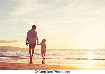 Father and Son Walking Together on the Beach at Sunset...