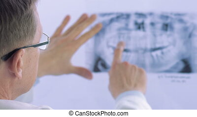 Closeup of dentist looking at dental x-ray plate. Dental...