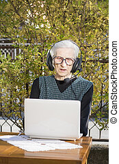 Senior woman having a video call on a notebook in the...