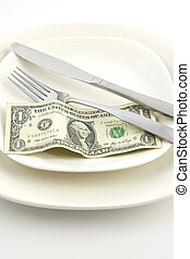 A United States one dollar bill on a white plate with a knife and fork