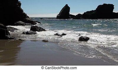 Waves On Sandy Beach With Rocks