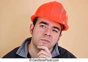 Contemplative Worker - A young construction working with a...