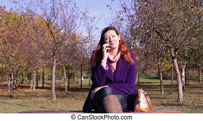 Woman in Park talking on a mobile phone - Woman talking on...
