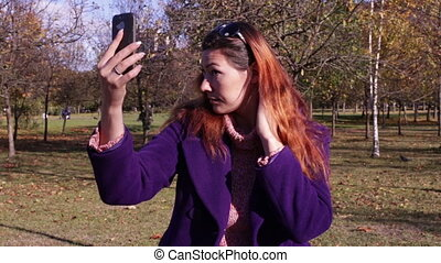 Woman taking self portrait using smartphone camera - A young...