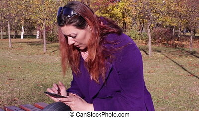Woman typing sms on your smartphone in the park