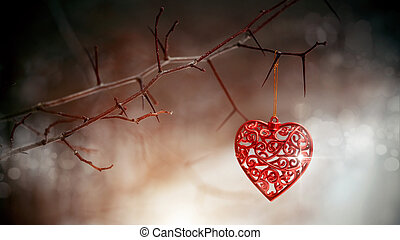 Red heart on prickly branches. Love symbol.