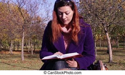 A woman reading a book on a park bench - Woman sitting on...