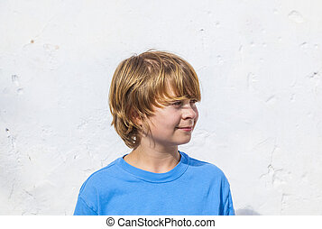 portrait of cute young boy in sunlight with white wall