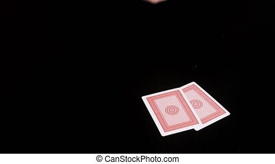 Hands on black table shuffling cards and dealing - Hands on...