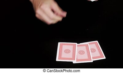 Hands on black table shuffling cards and dealing