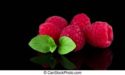 Raspberries with leaves isolated on black background