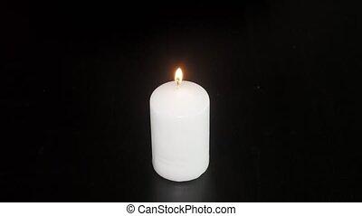 Extinguished candle closeup on black background