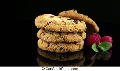 Dried fruits chip cookies and raspberries isolated on black...