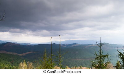 Clouds moving over the mountains. - Dark clouds moving over...