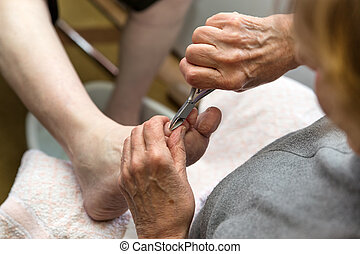 chiropodist with a nail scissors - a chiropodist with a nail...