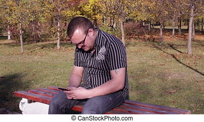 Man sits on a park bench and typing a sms on phone - Man...