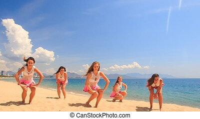 cheerleaders dance squat show poses on beach against sea -...