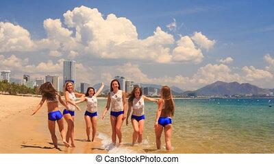 cheerleaders in uniform jump gambol wave hands in shallow...