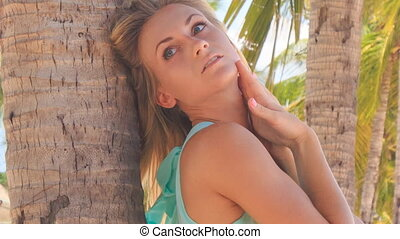 blonde girl in azure leans on palm trunk smoothes bust -...