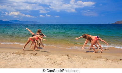 cheerleaders in bikinis perform hand scale stunt on wet sand...