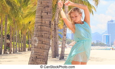 blonde girl in azure lifts hands smoothes brest among palms...