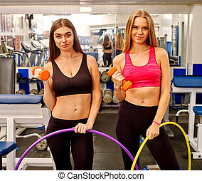 Group of people  working with dumbbells and hoop  at gym.