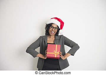 Young African American woman wearing a santa hat holding gift boxes